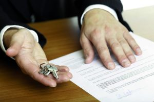 one hand of businessman gives  house keys to the hand of another businessman. Signed contract and pen visible in background.